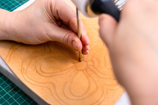 craftsman stamps the floral pattern on leather
