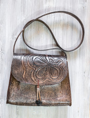 crossbody bag with stamped floral pattern on table