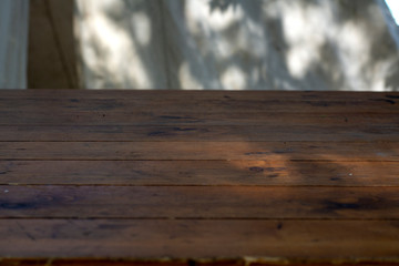 Wooden tabletop against a background of coarse white fabric
