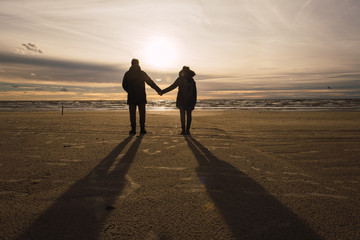 Couple holding hands on cold beach