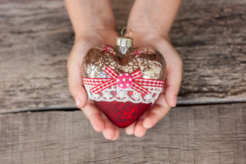 Christmas tree toy heart in the hands of a child. New Year. Christmas. Wooden Background. Toning light
