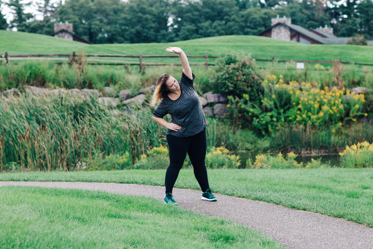Woman stretching arms on running path