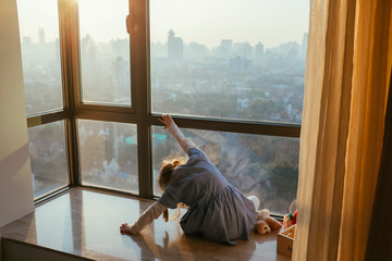 Young Girl on Windowsill with City View