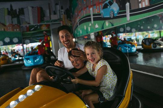 Dad and kids having fun on bumper cars