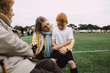 A young boy lacking confidence sits on his mothers lap for reassurance during a half time soccer break
