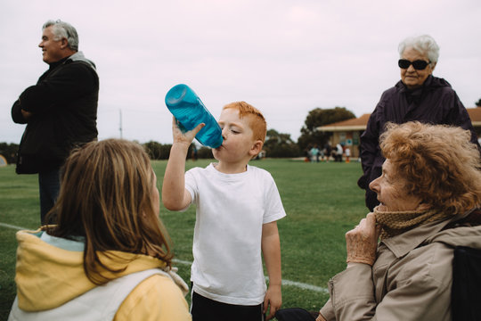 A young boy has a cold drink with his family during a half time break while playing sport