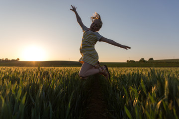 A little girl jumping in a field of wheat at sunset