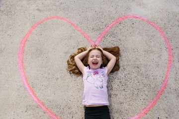Cute young girl laying in a chalk drawn heart on the ground
