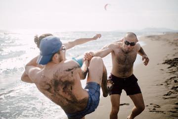 Friends having fun on the beach, wrestling