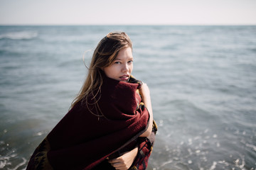 Portrait of a beautiful woman covered with blanket on the beach