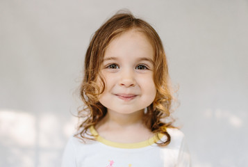 Adorable young girl with big cheeks smiling at the camera