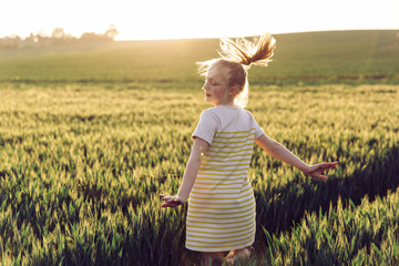 Female preteen child twirling in a wheat field at sunset