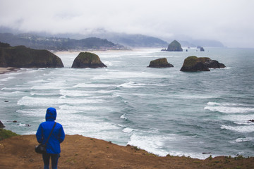 A person in a blue jacket stands overlooking the waves and rocks of Ecola State Park in Oregon