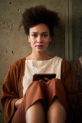 Young woman sitting, holding digital tablet in her hands