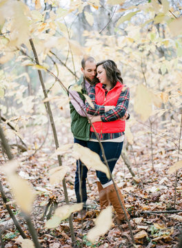 Engaged Couple Hiking in Woods