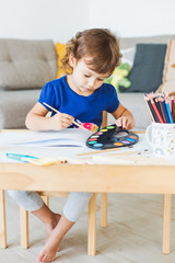 3 years girl painting at the small table at home.