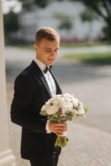 Happy groom in stylish suit take brides bouquet and smile