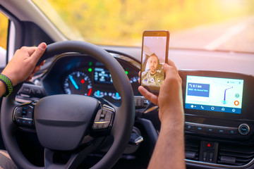 Male driver using smartphone to capture selfie pictures while driving