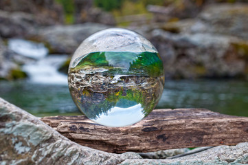 Crystal glass ball sphere reveals nature landscape in macro view