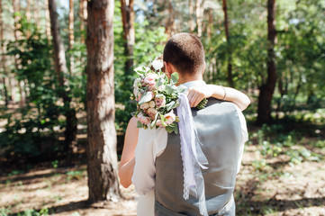 newlyweds hugging and standing in forest