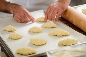 Man preparing croissants for baking