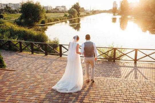 Beautiful newlyweds walking, holding hands, at sunset.