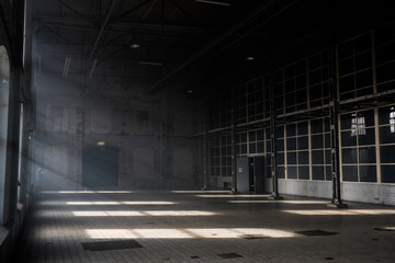 Sunlight shining throuh the windows of an old abandoned industrial warehouse building Wall mural