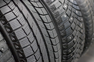 New black car tire, closeup.Brand new winter tires with a modern tread isolated.selective focus.Tire stack background.Winter season. Texture of car tire tread.