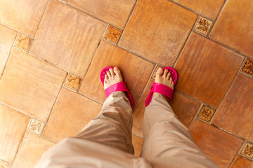 Pants covered legs extend to a pair of  white feet in red plastic slippers that are miss matched. The person is standing on a reddish brown tile floor.