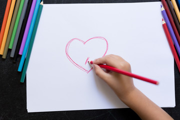 Kid's hand with pencil draws heart on white paper. Mother's day concept. Celebration. Hand made card.