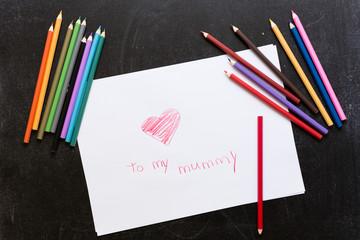Red heart on white paper drawn by pencil on black background. Pencils around. Love Mother's day concept. To my mummy words.