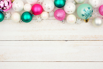 Pastel Christmas bauble top border over a bright white wood background