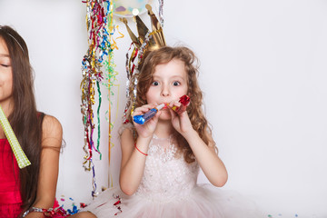 Holidays concept. Little funny girl with multicolored confetti on birthday party