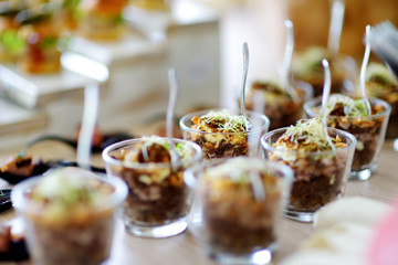 Fresh and delicious vegetable and pork salad served in mini glasses on a party or wedding reception.