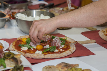 Pizza Maker who Prepares a Delicious Pizza with Bacon and Cherry Tomatoes