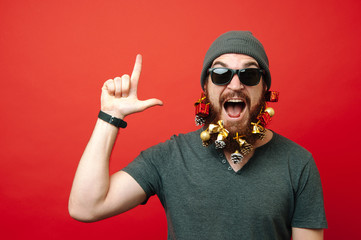 Excited man with decorated beard for christmas pointing up