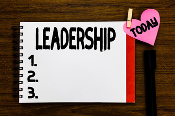Conceptual hand writing showing Leadership. Business photo text Ability Activity involving leading a group of showing or company Open notebook page markers holding paper heart wooden background
