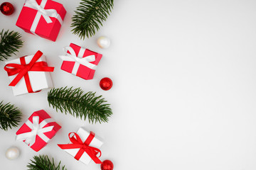 Christmas side border of red and white gift boxes with branches, top view over a white background