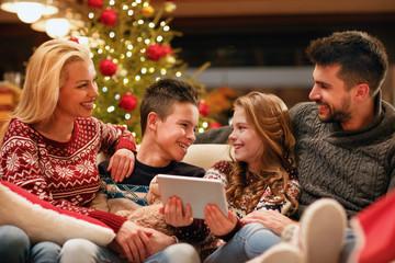 modern family having fun on digital tablet for Christmas.