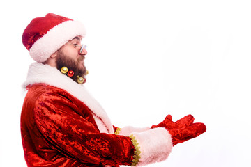 Happy in bespectacled Santa Claus  with decorations in a real beard  showing empty copy space on the open hand palm for text. Proposing product. Advertisement gesture presenting . Holding gift, text.