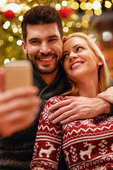 smiling woman and man in warm sweaters taking selfie picture with smartphone.