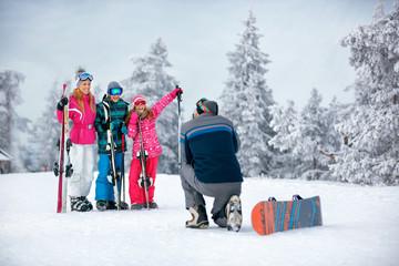 Ski, snow sun and fun - family on ski holiday taking picture