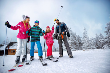 winter time and skiing - family with ski and snowboard on ski holiday in mountains