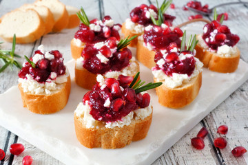 Holiday crostini appetizers with cranberries, pomegranates and feta cheese. Close up table scene on a white platter.