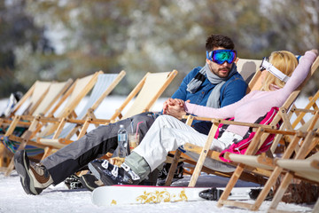 Woman and man resting in sun lounger