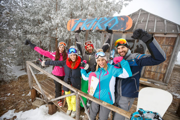 Group of snowboarders in winter wooden house