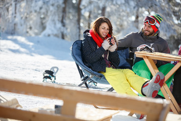 Skiers couple resting and drinking in cafe outdoor