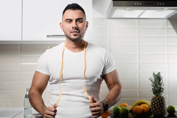 male dietitian in the kitchen with a measuring tape around his neck. The concept of a healthy lifestyle