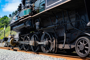Wheels of the retro locomotive with smoke and water vapor coming out of pipes.