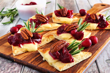 Spoed Fotobehang Voorgerecht Holiday flatbread appetizers with cranberries, pecans and brie cheese. Close up table scene on a wooden platter.